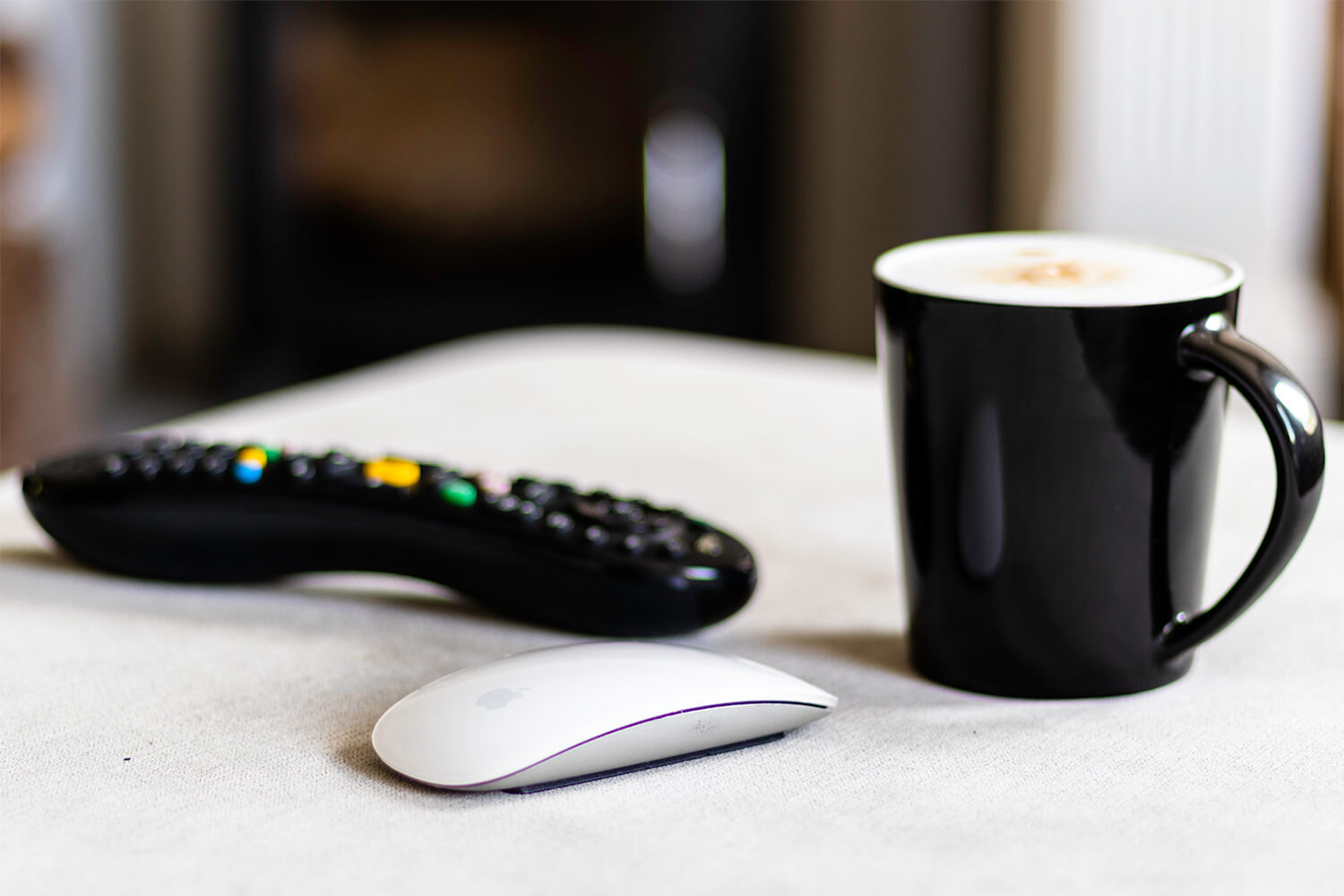 A magic mouse, cappucino and TV remote on a foot stool